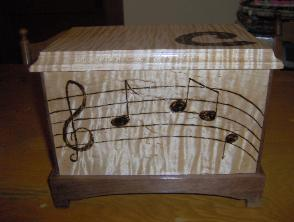 Box for my daughter.  Curly Maple with walnut base.  Musical motif hand burnt in.